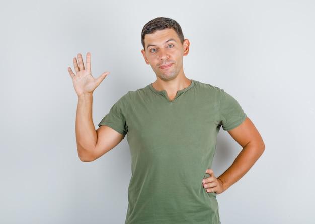 Молодой человек в зеленой футболке армии поднимает ладонь в жесте приветствия и выглядит позитивно.