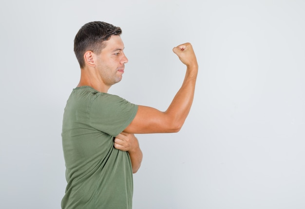 アーミーグリーンのtシャツの若い男が筋肉を示し、強い探しています。