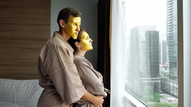 バスローブを着た若い男は、モダンなホテルの部屋の外の高層ビルと大きな窓の近くに金色のフェイスマスクでガールフレンドを抱きしめます
