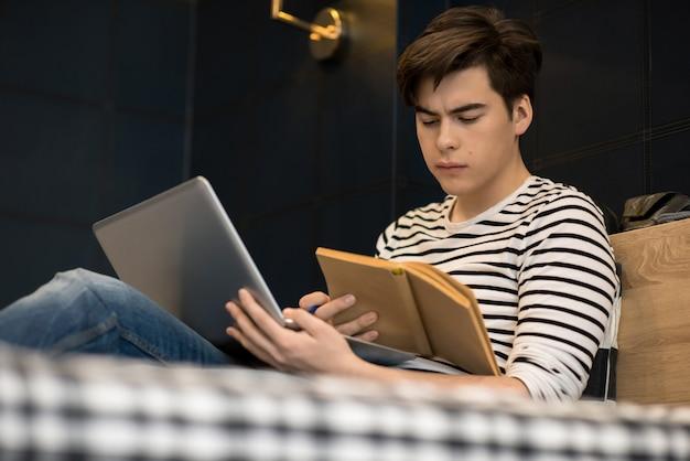Молодой человек в кровати читает книгу, держа ноутбук