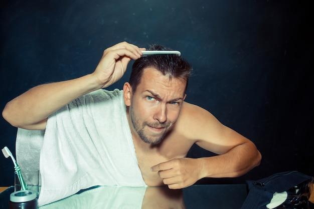 自宅で彼のひげを引っ掻く鏡の前に座っている寝室の若い男