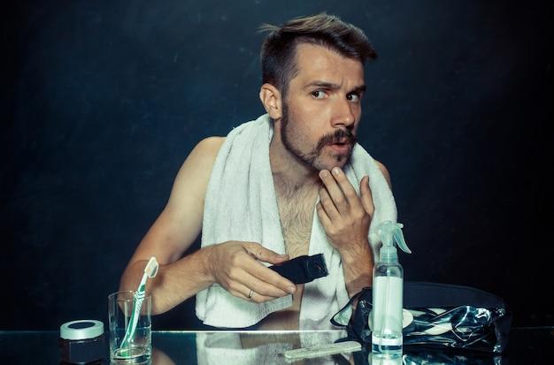 自宅で彼のひげを引っ掻く鏡の前に座っている寝室の若い男。人間の感情とライフスタイルの概念