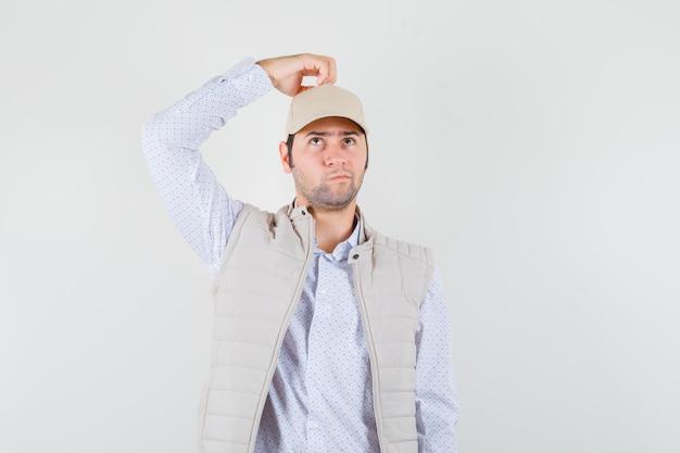 ベージュのジャケットと帽子をかぶった若い男が頭に手を持って、何かを考えて物思いにふける、正面図。