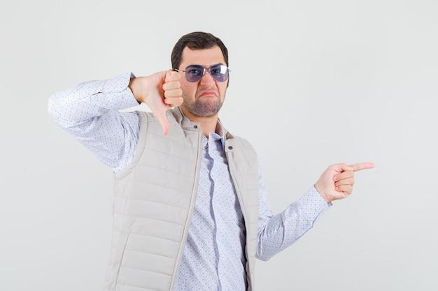 人差し指で右を指して、親指を下に向けて不機嫌そうに見える、正面図で眼鏡をかけているベージュのジャケットとキャップの若い男。