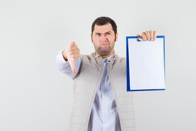 Молодой человек в бежевой куртке держит ноутбук и показывает большой палец вниз и выглядит недовольным, вид спереди.