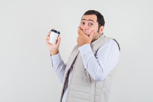 コーヒーのテイクアウトカップを保持し、手で口を覆い、驚いたように見えるベージュのジャケットの若い男、正面図。