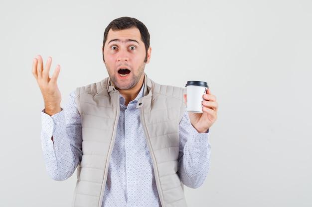 コーヒーのテイクアウトのカップを保持し、疑わしい方法で手を上げて、驚いたように見えるベージュのジャケットの若い男、正面図。