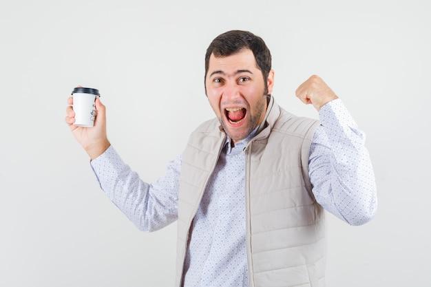 コーヒーのテイクアウトカップを保持し、勝者のポーズを示して、うれしそうに見えるベージュのジャケットの若い男、正面図。