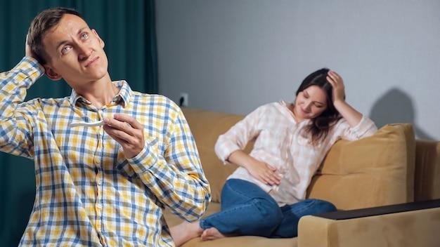 당황한 젊은 남자는 행복한 임산부의 배경에 있는 임신 테스트기를 본다