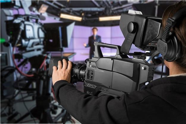 ニューススタジオで大きなビデオカメラを保持している黒い服を着た若い男