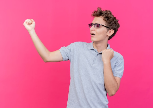 회색 폴로 셔츠를 입고 검은 안경에 젊은 남자가 분홍색 위에 행복하고 흥분된 주먹을 떨림
