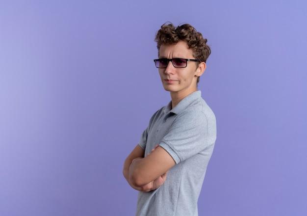파란색 벽 위에 서있는 가슴에 교차 손으로 불쾌한 회색 폴로 셔츠를 입고 검은 안경에 젊은 남자