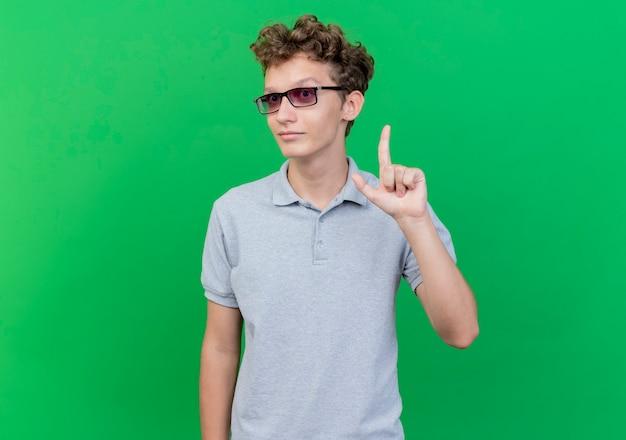 緑の壁の上に立っている新しいアイデアを持っている幸せでポジティブな人差し指を示す灰色のポロシャツを着ている黒い眼鏡の若い男
