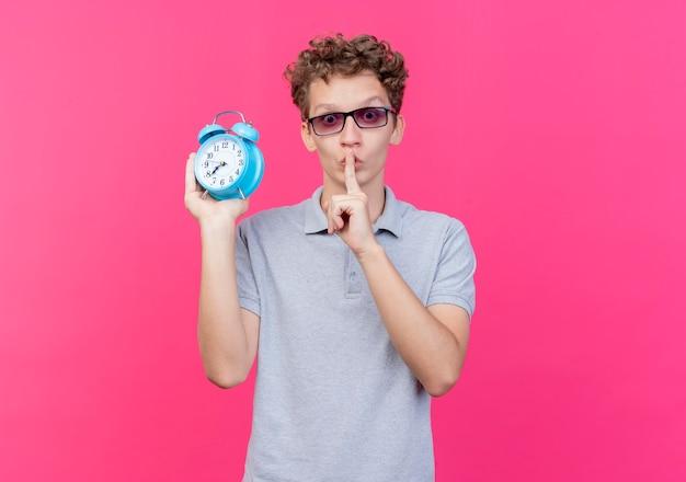 ピンクの壁の上に立っている唇に指で沈黙のジェスチャーを作る目覚まし時計を保持している灰色のポロシャツを着ている黒い眼鏡の若い男