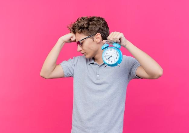 Молодой человек в черных очках в серой рубашке поло держит будильник, поднимает кулак, уверенно смотрит на розовый
