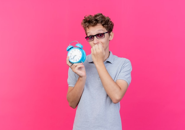 알람 시계를 들고 회색 폴로 셔츠를 입고 검은 안경에 젊은 남자가 핑크 이상 스트레스와 긴장