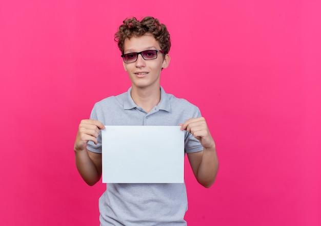 ピンクの壁の上に幸せで前向きに立って笑顔の白紙の紙を保持している灰色のポロシャツを着た黒い眼鏡の若い男
