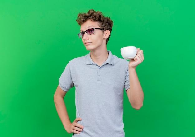 緑の壁の上に立って混乱し、不満を持って脇を見てコーヒーカップを保持している灰色のポロシャツを着た黒い眼鏡の若い男