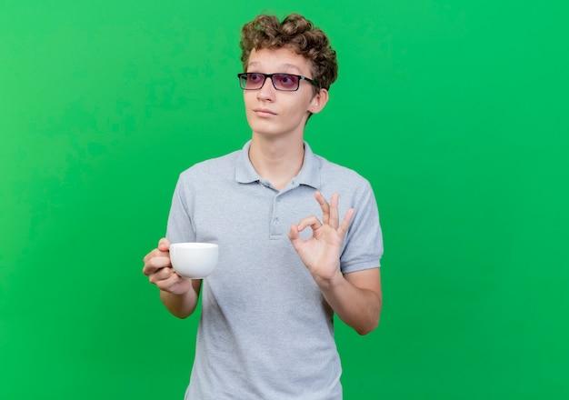緑の壁の上に立っている優れたokサインを見せて脇を見てコーヒーカップを保持している灰色のポロシャツを着ている黒い眼鏡の若い男