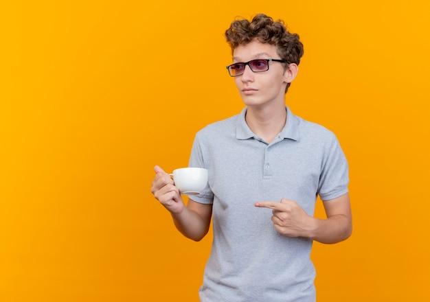 緑の壁の上に立っている深刻な顔で脇を見て指で指しているコーヒーカップを保持している灰色のポロシャツを着た黒い眼鏡の若い男