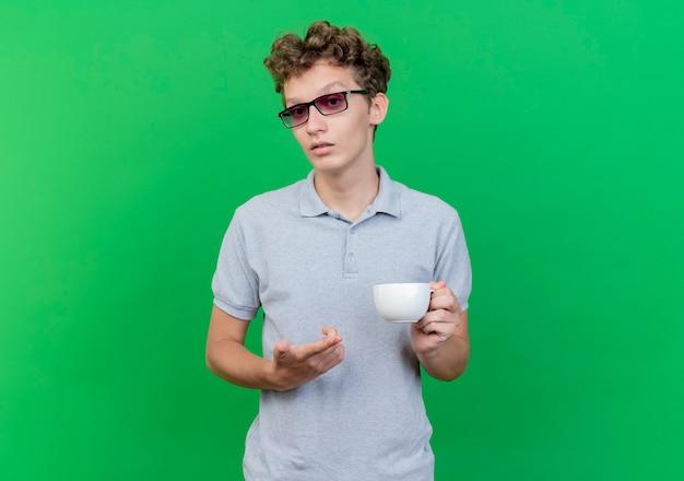 緑の壁の上に立っている懐疑的な表情で人差し指で指しているコーヒーカップを保持している灰色のポロシャツを着た黒い眼鏡の若い男