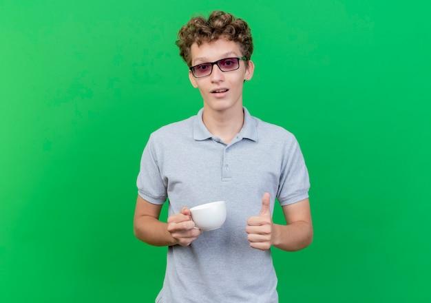 緑の壁の上に立って親指を見せて笑っているコーヒーカップを保持している灰色のポロシャツを着ている黒い眼鏡の若い男