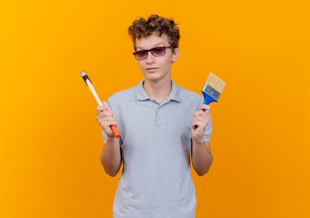 Молодой человек в черных очках в серой рубашке поло держит молоток и кисть с серьезным лицом над оранжевым