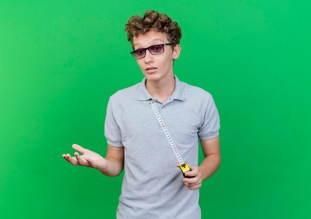 緑の壁の上に立って混乱している手で身振りで示すメジャーテープを保持している灰色のポロシャツを着ている黒い眼鏡の若い男