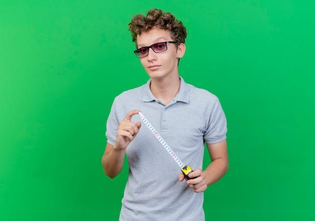 緑の壁の上に幸せで前向きに立って笑顔のメジャーテープを保持している灰色のポロシャツを着た黒い眼鏡の若い男