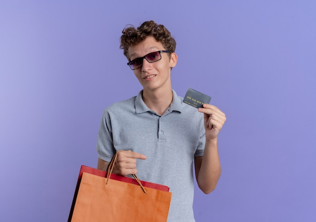 青い壁の上に立ってクレジットカードの笑顔を示す紙袋を保持している灰色のポロシャツを着た黒い眼鏡の若い男