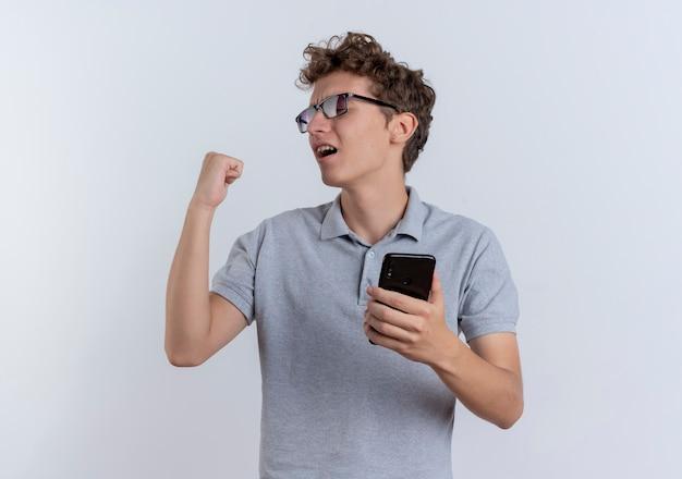 灰色のポロシャツを着た黒い眼鏡の若い男がスマートフォンを握りこぶしを握りしめて幸せで白に興奮