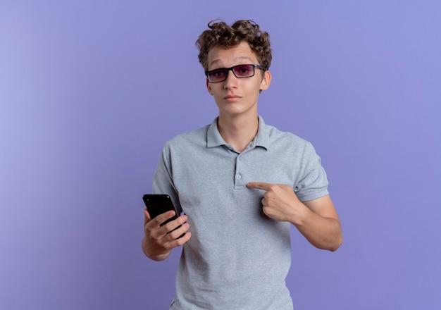 青い壁の上に立って混乱している自分を指しているスマートフォンを保持している灰色のポロシャツを着た黒い眼鏡の若い男
