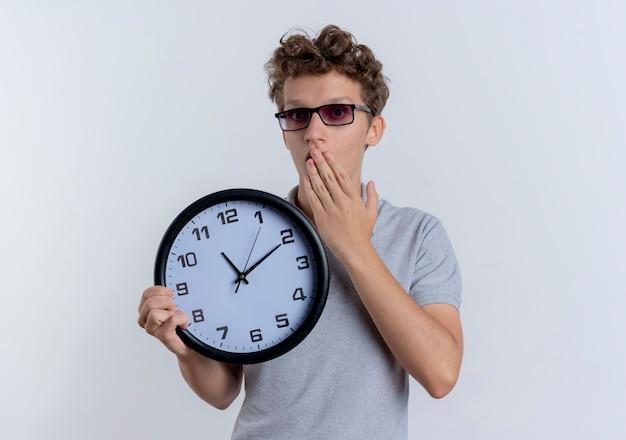 회색 폴로 셔츠를 입고 검은 안경에 젊은 남자가 흰 벽 위에 서 충격을 받고 손으로 입을 덮고 벽 시계를 들고