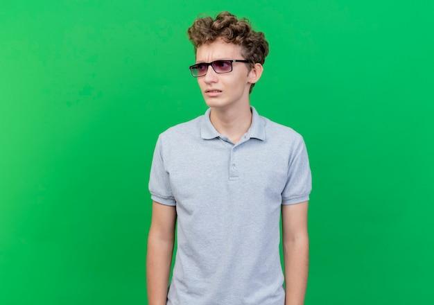 Молодой человек в черных очках, одетый в серую рубашку поло, смотрит в сторону, обеспокоенный и сбитый с толку, стоит у зеленой стены