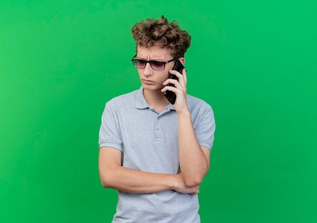 緑の上で携帯電話で話している間、脇を見て混乱している灰色のポロシャツを着た黒い眼鏡の若い男
