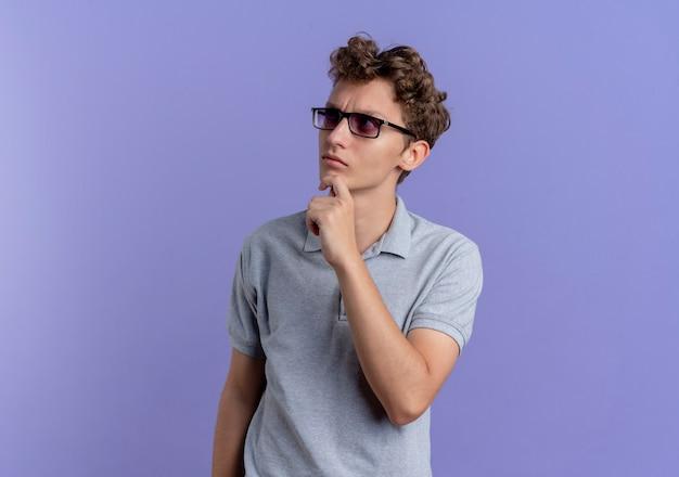 青い壁の上に立って困惑して脇を見ている灰色のポロシャツを着た黒い眼鏡の若い男