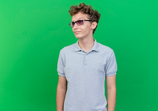 緑の壁の上に立っている顔に笑顔で脇を見て灰色のポロシャツを着た黒い眼鏡の若い男