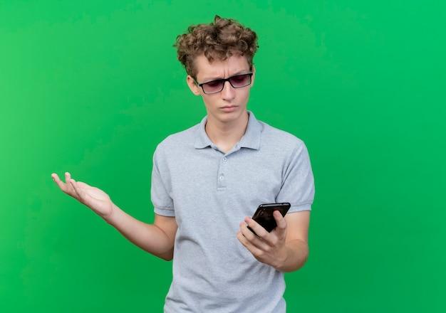 緑の壁の上に立って不機嫌と混乱している彼のスマートフォンの画面を見ている灰色のポロシャツを着た黒い眼鏡の若い男