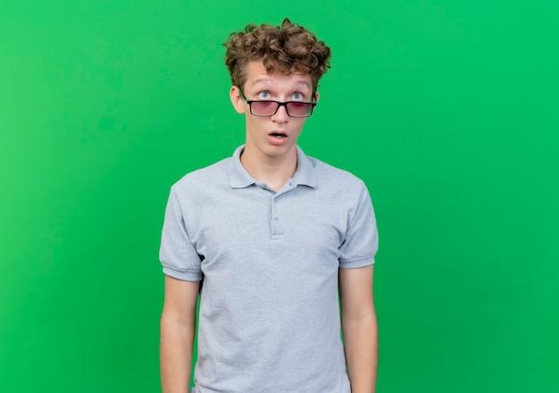 Молодой человек в черных очках, одетый в серую рубашку поло, удивленно смотрит вверх над зеленым