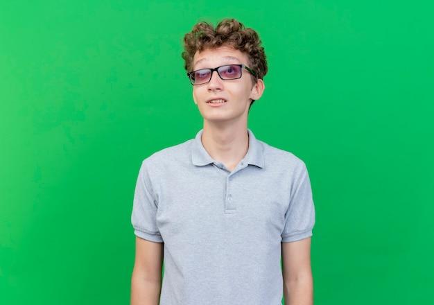 Молодой человек в черных очках в серой рубашке поло смотрит вверх, улыбаясь, стоя у зеленой стены