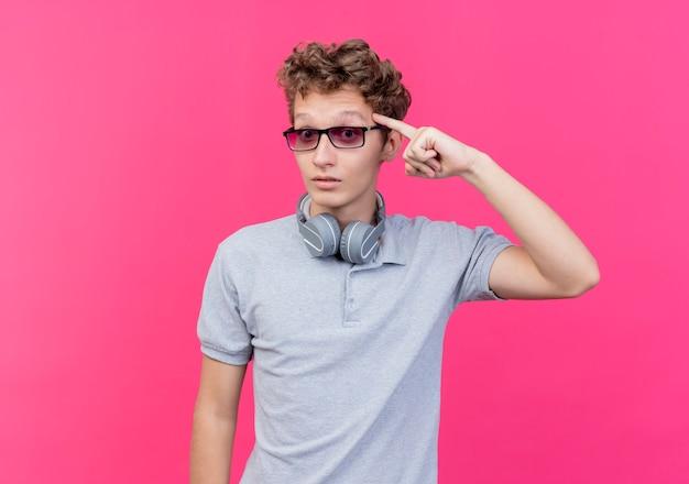 ピンクの壁の上に立っているタスクに焦点を当てた彼の寺院を指している灰色のポロシャツを着た黒い眼鏡の若い男