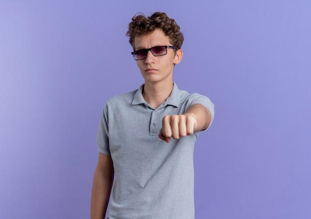 青い壁の上に立っている真面目な顔で拳を指して灰色のポロシャツを着た黒い眼鏡の若い男