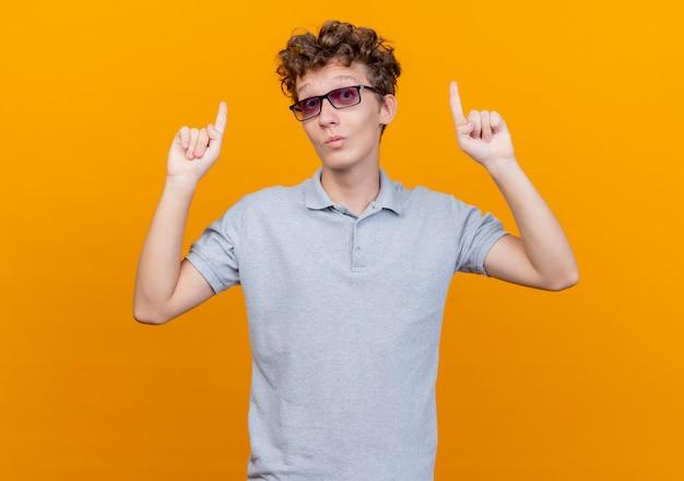 주황색 벽 위에 서서 놀란 idex 손가락으로 가리키는 회색 폴로 셔츠를 입고 검은 안경에 젊은 남자