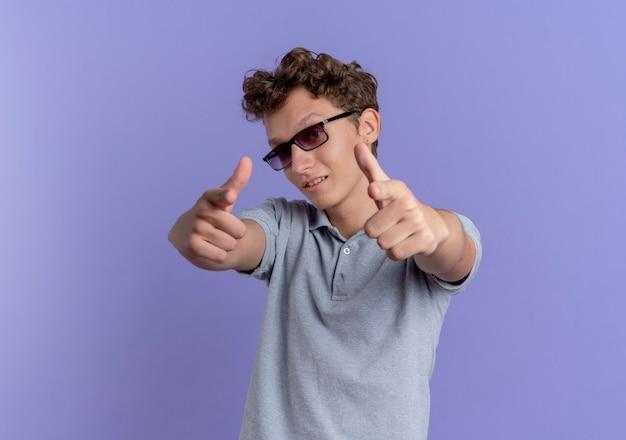 青い壁の上に立って自信を持って見える人差し指で指している灰色のポロシャツを着た黒い眼鏡の若い男