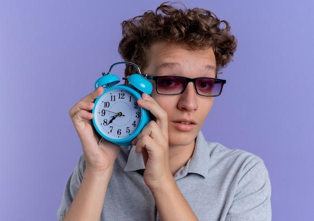 青い壁の上に立って混乱している目覚まし時計を示す灰色のポロシャツを着た黒い眼鏡の若い男