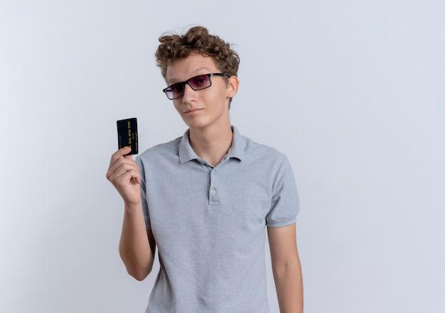 白い壁の上に立って自信を持って見えるクレジットカードを示す灰色のポロシャツを着た黒い眼鏡の若い男