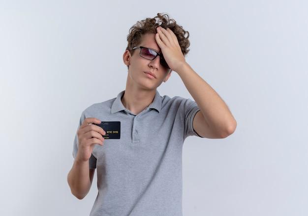 灰色のポロシャツを着た黒い眼鏡の若い男は、白い壁の上に立って混乱し、非常に心配そうに見えるクレジットカードを示しています