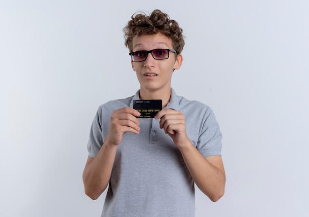 白い壁の上に立って驚いたクレジットカードを示す灰色のポロシャツを着た黒い眼鏡の若い男