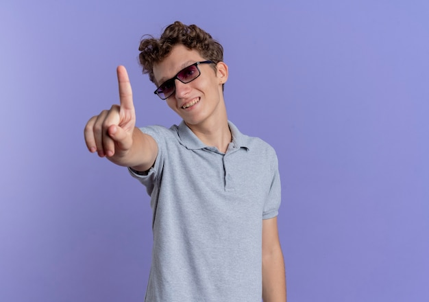 青い壁の上に立っている幸せそうな顔で笑顔の人差し指を示す灰色のポロシャツを着た黒い眼鏡の若い男