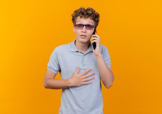 オレンジ色の壁の上に立って驚いて見える携帯電話で話している灰色のポロシャツを着た黒い眼鏡の若い男